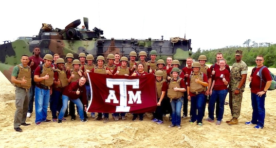 Lt. Col. Carlos T. Jackson, right, and retired Lt. Col. Chris Emmerson, far left, pose with students from the Texas A&M Corps of Cadets in front of an Amphibious Assault Vehicle assigned to Combat Assault Battalion, 3rd Marine Division, May 18, 2016, at Camp Schwab, Okinawa, Japan. The Cadets visited Okinawa as part of a scholarship program which provides students the opportunity to tour military installations to learn about different occupational specialties and duty stations. This is the first time Texas A&M Corps of Cadets visited Okinawa.