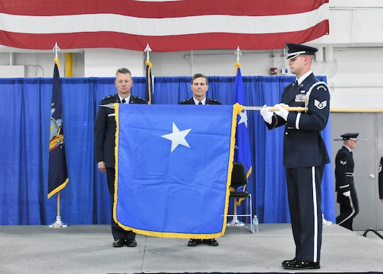 Maj. Gen. Anthony German (left), the Adjutant General of the State of New York and Brig. Gen. Greg Semmel (right) stand for the unfurling of the brigadier general flag, during his promotion ceremony held on Hancock Field in Syracuse, NY Friday, June 10. Semmel will now serve as Assistant Adjutant General – Air for the New York Air National Guard. (U.S. Air National Guard photo by Tech. Sgt. Jeremy M. Call/Released)