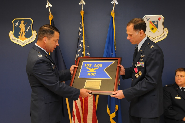 New York Air National Guard Col. Michael Comella (right) receives an award from the new Commander of the 152nd Air Operations Group, Col. Brian VanKouwenberg (left) as a token of appreciation for his 30 years of service, during a retirement  ceremony held on Hancock Field in Syracuse, NY, Saturday, June 11. (U.S. Air National Guard photo by Tech. Sgt. Justin A. Huett/Released)