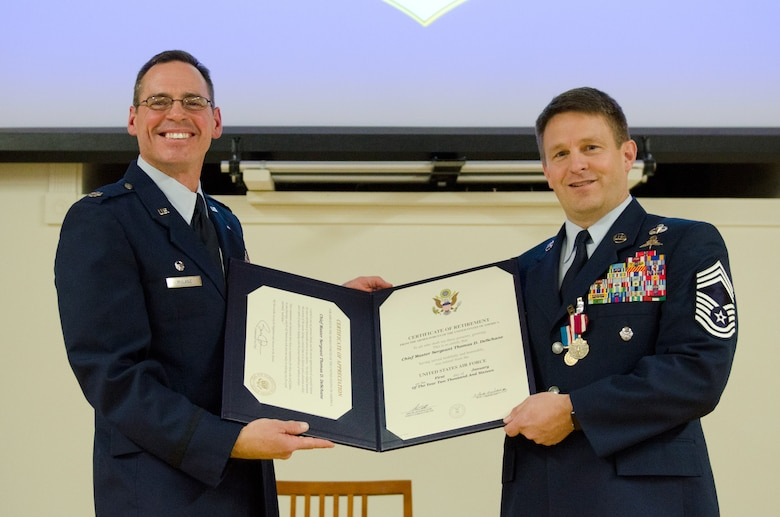 Chief Master Sgt. Thomas DeSchane (right), the outgoing chief enlisted manager for the 123rd Special Tactics Squadron, is presented with his Certificate of Retirement by Lt. Col. Sean McLane, squadron commander, during DeSchane's retirement ceremony at the Kentucky Air National Guard Base in Louisville, Ky., Dec. 5, 2015. DeSchane is retiring after more than 28 years of service to the active-duty Air Force and Air National Guard. (U.S. Air National Guard photo by Senior Airman Joshua Horton)