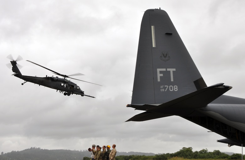 Reservists from the 304th Rescue Squadron, Portland Air National Guard Base, Ore., stand behind an HC-130 as they watch an HH-60G Pave Hawk helicopter from the 305th Rescue Squadron, Davis-Monthan Air Force Base, Ariz., depart the airport in Astoria, Ore., June 8, 2016. Several 304th personnel, plus Air and Army National Guardsmen and other local, state and federal government and civilian organizations participated in Cascadia Rising, a disaster response exercise simulating a magnitude 9.0 earthquake and subsequent tsunami in the Pacific Northwest. (U.S. Air Force photo by 1st Lt. Anna-Marie Wyant)