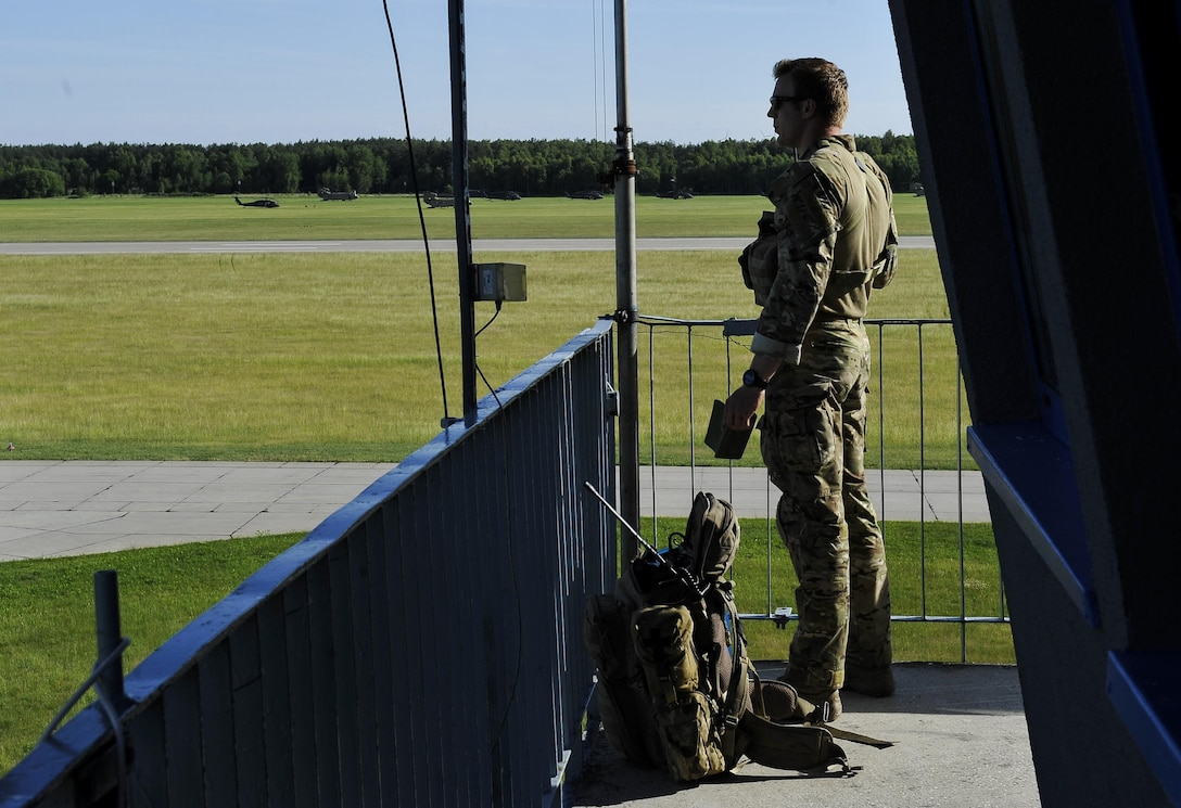 A tactical air control party Airman from the 4th Air Support Operations Squadron observes the airfield as he communicates with ground forces during Exercise Anakonda 2016 June 9, 2016, at Swidwin Air Base, Poland. Exercise Anakonda 2016 is a Polish-led exercise, involving several nations, with over 25,000 participants from more than 20 countries. (U.S. Air Force photo/Airman 1st Class Lane T. Plummer)
