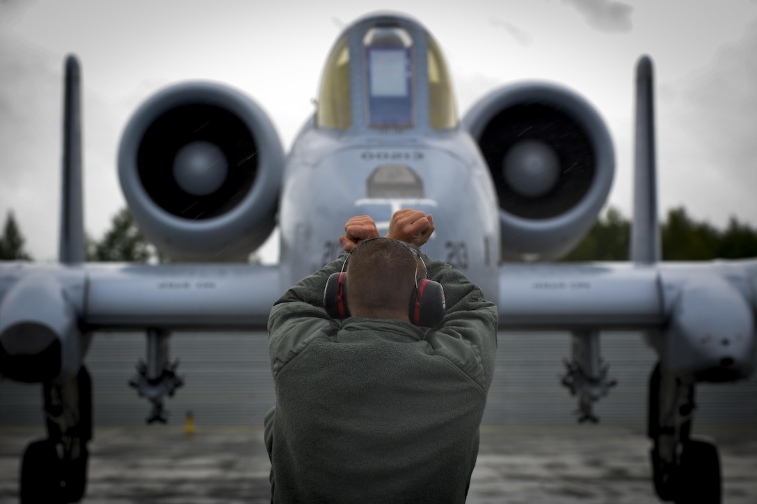 A crew chief guides an A-10C Thunderbolt II pilot into parking position at Lielvarde Air Base, Latvia June 11, 2016.  Members of the 107th Fighter Squadron, Selfridge Air National Guard Base, Michigan join other U.S. armed forces and Latvian airmen to participate in Saber Strike 16; a long-standing, U.S. Joint Chiefs of Staff-directed, U.S. Army Europe-led cooperative-training exercise, which has been conducted annually since 2010. This year's exercise will focus on promoting interoperability with allies and regional partners.  (U.S. Air Force photo/Senior Airman Nicole Keim)