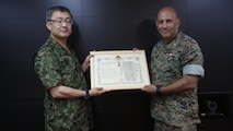 U.S. Marine Col. Eric M. Mellinger, right, receives a certificate of appreciation and a Defense Cooperation Medal from Japanese Ground Self-Defense Force Col. Shusei Hotta on behalf of Gen. Kiyofumi Iwata, June 13, 2016, at Camp Courtney, Okinawa, Japan. Mellinger was awarded for significantly contributing to increased training opportunities for the JGSDF by advancing co-use of Marine Corps training facilities on Okinawa and expanding III Marine Expeditionary Force efforts to participate in alliance/bilateral exercises. Hotta is the deputy chief of Policy and Programs Division, Ground Staff Office, JGSDF. Iwata is JGSDF chief of staff. Mellinger is III MEF chief of staff.