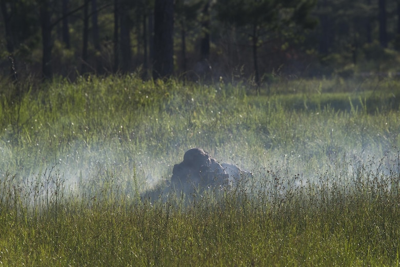 A Marine with 3rd Battalion, 6th Marine Regiment lays in the cover of smoke from a simulation artillery round during the battalions Marine Corps Combat Readiness Evaluation, at Camp Lejeune, N.C.,  June 10, 2016. The MCCRE, a pre deployment exercise, tests the Marines on operational readiness and their ability to operate as a whole.