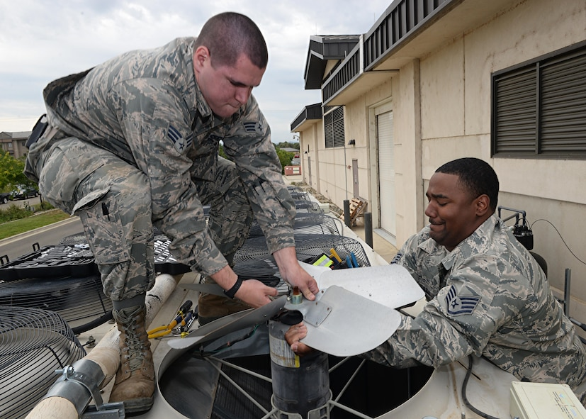 9th Civil Engineer Squadron Heating, Ventilation and Air Conditioning technicians Senior Airman Kyle Cvoliga (left) and Staff Sgt. Yohance Leslie remove a fan and its motor from a HAVC unit May 24, 2016, at Beale Air Force Base, California. The 9th CES HVAC flight maintains the temperature of the operational systems to the Distributed Ground System-2, the RQ-4 Global Hawk fleet's flight shelters and other global combat influences. If those temperatures rise too high it can cause a halt in mission support.  (U.S. Air Force photo by Senior Airman Ramon A. Adelan)