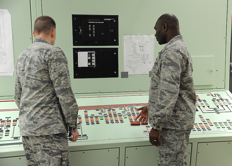 Lt. Col. John Koehler, 10th Space Warning Squadron commander, left, and Col. Rodney Lewis, 319th Air Base Wing commander, right, examine an electrical monitoring system June 11, 2016, on Cavalier Air Force Station, N.D. Community members were given the opportunity to tour the Perimeter Acquisition Radar Attack Characterization System during the Cavalier AFS open house. (U.S. Air Force photo by Senior Airman Ryan Sparks/Released)