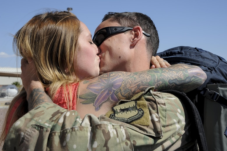 U.S. Air Force Staff Sgt. Scott, assigned to the 48th Rescue Squadron, embraces his wife after returning home from a 4-month-long deployment at Davis-Monthan Air Force Base, Ariz., June 8, 2016. Two of the three 48th RQS rescue teams, as well as a support team, returned home from a 4-month-long deployment to Turkey. (U.S. Air Force photo by Airman 1st Class Mya M. Crosby/Released)