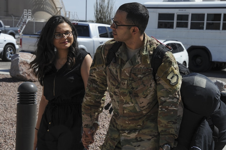U.S. Air Force Staff Sgt. Julius, assigned to the 48th Rescue Squadron, greets his wife after returning home from a 4-month-long deployment at Davis-Monthan Air Force Base, Ariz., June 8, 2016. The 48th RQS's mission is to deploy forces worldwide in support of national security and homeland defense while providing highly trained personnel who are capable of quickly and effectively executing recovery operations. (U. S. Air Force photo by Airman 1st Class Mya M. Crosby/Released)