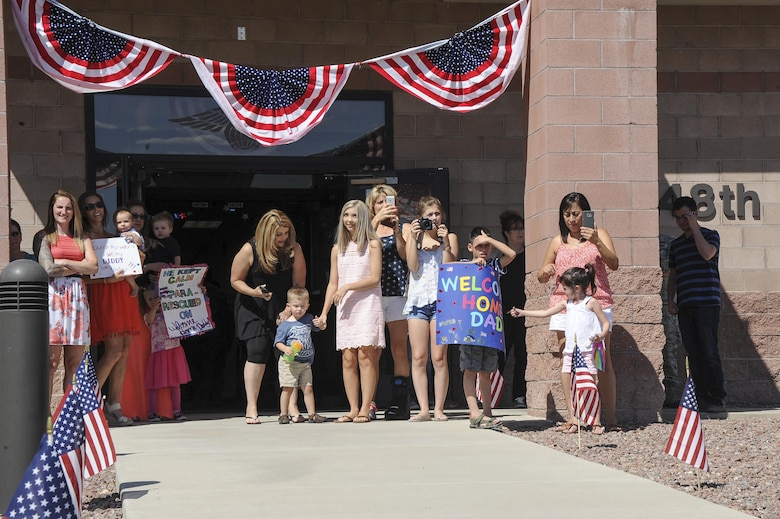 Families wait for the arrival of members assigned to the 48th Rescue Squadron to return home from deployment at Davis-Monthan Air Force Base, Ariz., June 8, 2016. The 48th RQS Airmen were deployed to Turkey in support of Combined Joint Task Force - Operation Inherent Resolve. (U.S. Air Force photo by Airman 1st Class Mya M. Crosby/Released)
