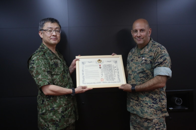 CAMP COURTNEY, Okinawa, Japan - U.S. Marine Col. Eric M. Mellinger, right, receives a certificate of appreciation and a Defense Cooperation Medal from Japanese Ground Self-Defense Force Col. Shusei Hotta on behalf of Gen. Kiyofumi Iwata, June 13, 2016, at Camp Courtney, Okinawa, Japan. Mellinger was awarded for significantly contributing to increased training opportunities for the JGSDF by advancing co-use of Marine Corps training facilities on Okinawa and expanding III Marine Expeditionary Force efforts to participate in alliance/bilateral exercises. Hotta is the deputy chief of Policy and Programs Division, Ground Staff Office, JGSDF. Iwata is JGSDF chief of staff. Mellinger is III MEF chief of staff.