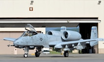 "A U.S. Air Force A-10 Thunderbolt II pilot assigned to the 354th Fighter Squadron (FS) out of Davis-Monthan Air Force Base, Ariz., taxis her twin-engine, ground-attack aircraft out of a hangar on Eielson Air Force Base, Alaska, June 6, 2016, during RED FLAG-Alaska (RF-A) 16-2. RF-A is a series of Pacific Air Forces commander-directed field training exercises that enable U.S. and partner nation forces like the 354 FS ""Bulldogs"" to sharpen their combat skills by flying simulated combat sorties in a realistic threat environment inside the more than 67,000 square mile Joint Pacific Alaska Range Complex, the largest instrumented air, ground and electronic combat training range in the world. (U.S. Air Force photo by Master Sgt. Karen J. Tomasik/Released)"