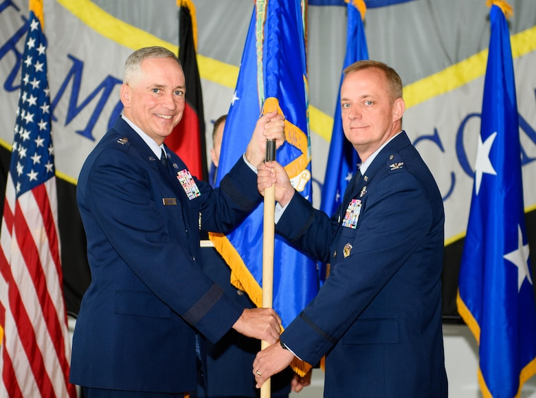 Maj. Gen. Frederick Martin, U.S. Air Force Expeditionary Center commander, passes the 521st Air Mobility Operations Wing flag to Col. Thomas Cooper during a change-of-command ceremony at Ramstein Air Base, Germany, June 14, 2016. With the passing of the flag, Cooper took command of more than 2,000 Airmen throughout Europe and Africa. (U.S. Air Force photo/Staff Sgt. Armando A. Schwier-Morales)
