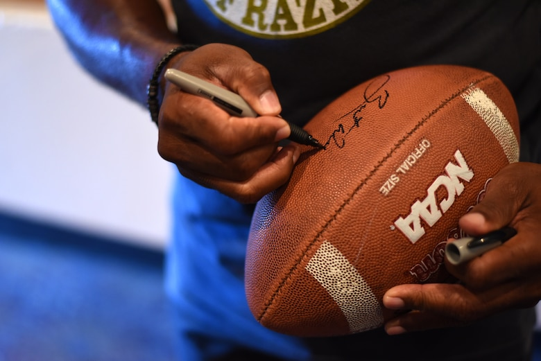 PETERSON AIR FORCE BASE, Colo. – Herschel Walker, retired NFL football player, signs autographs for Team Pete in the base auditorium at Peterson Air Force Base, Colo. on June 8, 2016. Walker was elected to the College Football Hall of Fame in 1999 and is widely regarded as one of college football's greatest players. (U.S. Air Force photo by Airman 1st Class Dennis Hoffman)