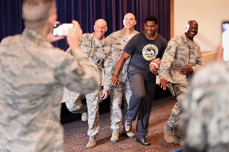 PETERSON AIR FORCE BASE, Colo. – Herschel Walker, retired NFL football player, strikes the Heisman pose with Team Pete service members in the base auditorium at Peterson Air Force Base, Colo. on June 8, 2016. Walker played college football for the University of Georgia, earned consensus All-American honors three times and won the 1982 Heisman Trophy. (U.S. Air Force photo by Airman 1st Class Dennis Hoffman)