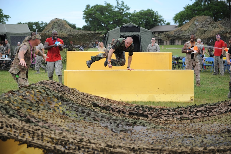 Capt. Harlan Glinski, 81st Security Forces Squadron operations officer, jumps over barriers during the 81st Mission Support Group Combat Dining In June 10, 2016, Keesler Air Force Base, Miss. The Combat Dining-In is a military tradition that promotes camaraderie and esprit de corps throughout the ranks. (U.S. Air Force photo by Kemberly Groue)