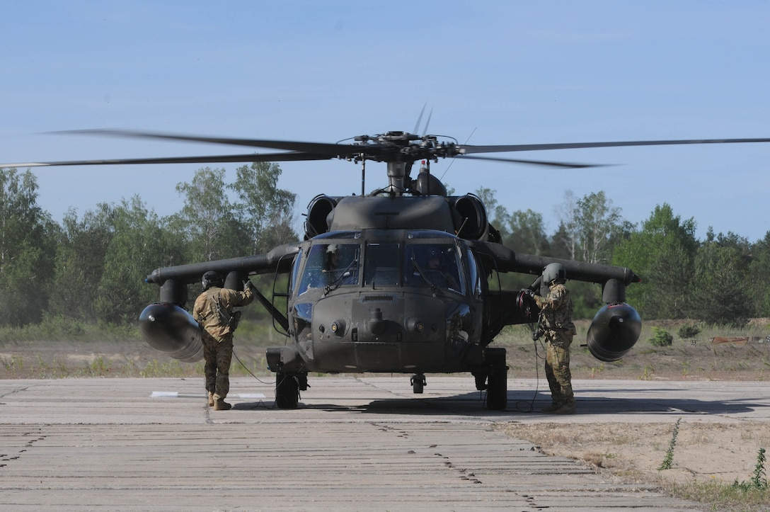 Two UH-60 Blackhawks crew members with the 1-214th Aviation Regiment, Alpha Company, prepare to unload passengers in Warsaw, Poland, June 9, as part of the training exercise Anakonda 2016. Anakonda 2016 is one of U.S. Army Europe's premier multinational training events, which features 24 nations and seeks to train, exercise and integrate Polish national command and force structures into an allied, joint, multinational environment.