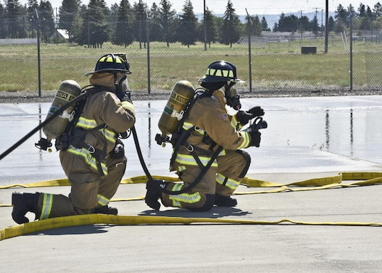 Staff Sgt. Michael Granados and Staff Sgt. Kari Dudoit, 92nd Civil Engineer Squadron firefighters, prepare to shoot water during an exercise with the Spokane International Airport June 9, 2016, in Spokane, Wash. The exercise included more than 40 local emergency responders from around the county to include: Spokane International Airport Fire and Rescue, Spokane International Airport Police Department, Spokane Fire Department, Fairchild Air Force Base Fire Department, Spokane County Fire District 10 and American Medical Response. (U.S. Air Force photo/Airman 1st Class Taylor Shelton)