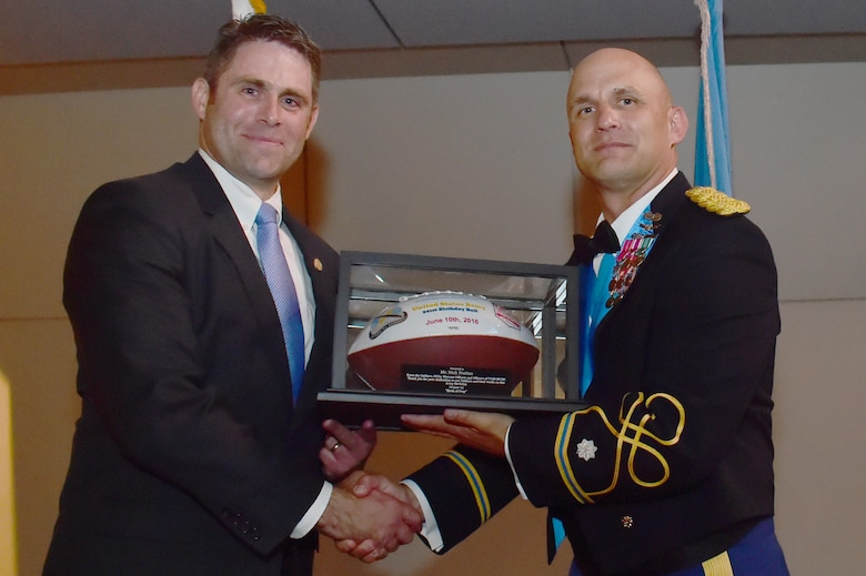 U.S. Army Lt. Col. Andrew Pekala, 743rd Military Intelligence Battalion commander, hands a recognition gift to guest speaker Nicholas Freitas, Virginia House of Delegates member, June 10, 2016, at Sports Authority Field at Mile High in Denver, during the 743rd Military Intelligence Battalion's Army Ball. The 743rd MIB celebrated the 241st birthday of the U.S. Army. (U.S. Air Force photo by Airman 1st Class Luke W. Nowakowski/Released)