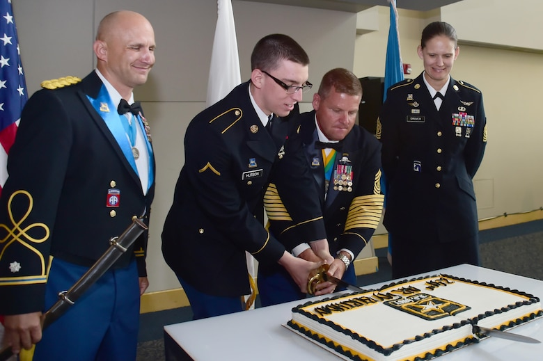 U.S. Army Sgt. Maj. Ramond Ramsey, 743rd Military Intelligence Battalion, and Pvt. Jacob Hudson, 743rd MIB analyst, cut the cake in celebration of the Army's 241st birthday June 10, 2016, at Sports Authority Field at Mile High in Denver. The 743rd MIB held their annual ball which recognizes the U.S. Army's birthday each year. (U.S. Air Force photo by Airman 1st Class Luke W. Nowakowski/Released)