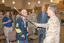 Brig. Gen. John Kolasheski, former deputy commanding general for maneuver, 1st Infantry Division, knights retired 1st Sgt. Albert Curley, former Buffalo Soldier, as he is inducted into the Order of St. George May 23. The United States Armor Association established The Order of St. George in 1986 as a way to recognize the very best tankers and cavalrymen amongst its ranks for their outstanding performance.