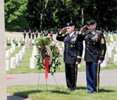 "Maj. Gen. Wayne W. Grigsby Jr., 1st Infantry Division and Fort Riley commanding general, left, and Command Sgt. Maj. Jonathan D. Stephens, 1st Infantry Division Artillery, right, salute the memorial wreath May 30 during the Memorial Day ceremony at Fort Riley. The wreath bares the inscription, ""lest we forget."""