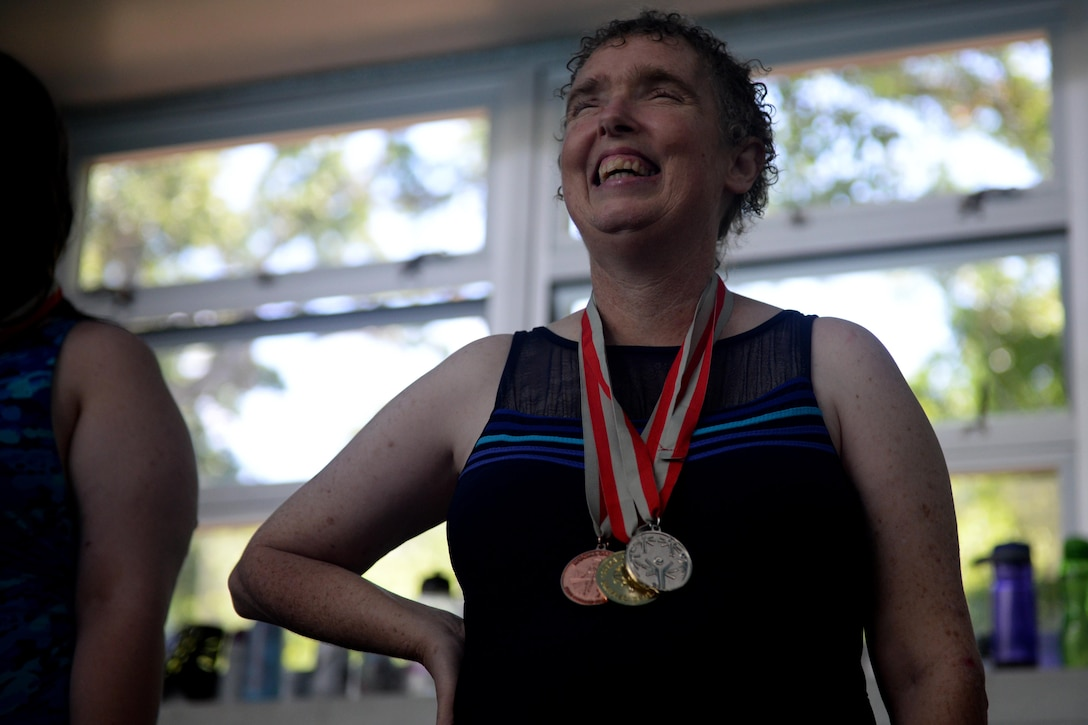 Paula Carpenter, District 5 Special Olympics Mississippi athlete, stands on the podium after receiving a medal at the Biloxi Natatorium May 21, 2016, Biloxi, Miss. Carpenter has been competing in SOMS for more than 25 years. This year she earned bronze in the 25 meter freestyle relay, silver in the 50 meter freestyle and gold in the 50 meter backstroke. (U.S. Air Force photo by Airman 1st Class Travis Beihl)