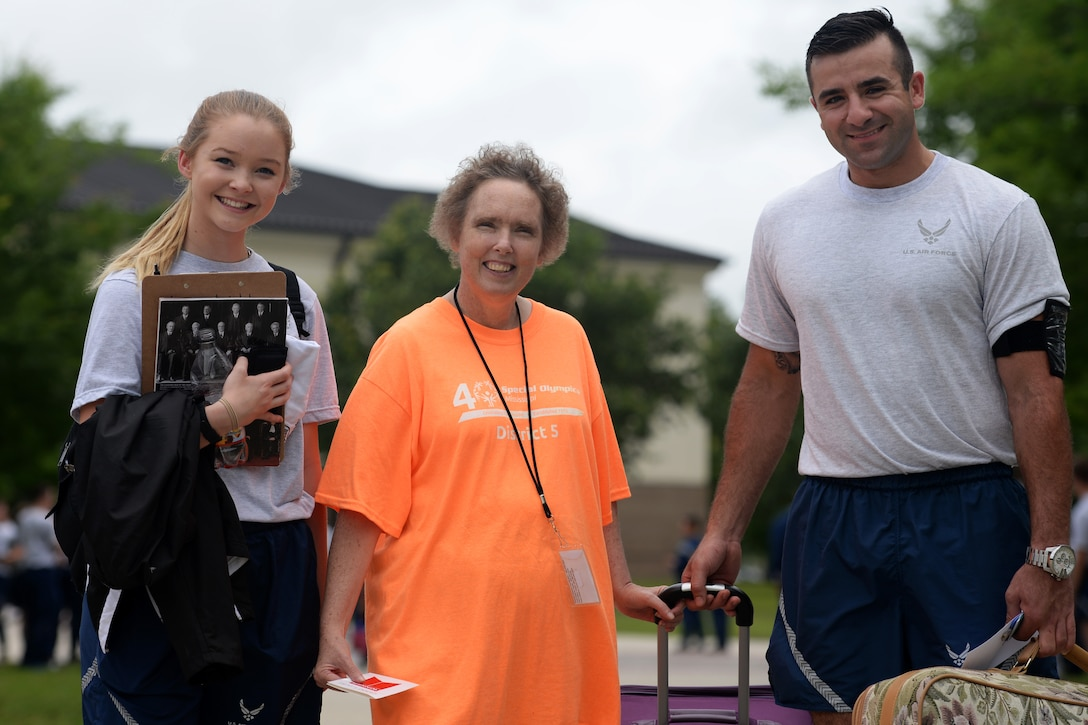 Airman Basic Ashlyn Tran and Senior Airman Hashim Mefleh, 336th Training Squadron students, help Paula Carpenter, District 5 Special Olympics Mississippi athlete, with her luggage May 20, 2016, Keesler Air Force Base, Miss. Carpenter has competed in SOMS for more than 25 years and this year Tran and Mefleh are her Airman sponsors. (U.S. Air Force photo by Airman 1st Class Travis Beihl)