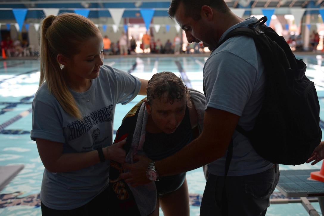 Airman Basic Ashlyn Tran and Senior Airman Hashim Mefleh, 336th Training Squadron students, aid Paula Carpenter, District 5 Special Olympics Mississippi athlete, after finishing the 50 meter backstroke at the Biloxi Natatorium May 21, 2016, Biloxi, Miss. Carpenter has competed in SOMS for more than 25 years and this year Tran and Mefleh are her Airman sponsors helping her compete in three aquatics events. (U.S. Air Force photo by Travis Beihl)