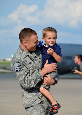Master Sgt. Robert Mills of the 507th Maintenance Squadron at Tinker Air Force Base, Okla., holds his oldest son moments after returning from a four-month deployment from Southwest Asia June 11, 2016. Moments later, he met his two-month old son for the first time. (U.S. Air Force photo/Tech. Sgt. Lauren Gleason)