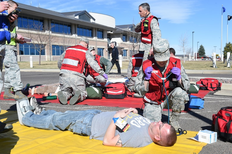 Staff Sgt. Neah Howard, 460th Medical Group medical standards NCO in charge, attends to the simulated injuries of Team Buckley members during the Panther Lighting exercise March 25, 2015, on Buckley Air Force Base, Colo. Panther Lightning is Buckley AFB's version of the Strategic Command exercise, Global Lightning, which is an Air Force-wide exercise that focuses on all combatant commands and their missions.