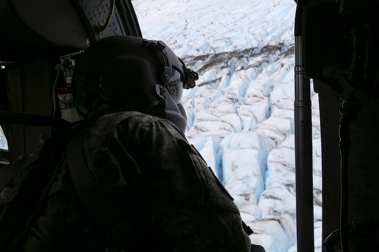 Alaska Army National Guard UH-60 Black Hawk helicopter crew chief, Sgt. Sonny Cooper, assigned to the 1st Battalion, 207th Aviation Regiment, surveys a potential landing site on Colony Glacier, Alaska, June 4, 2016. In November 1952, an Air Force C-124 Globemaster II crashed into nearby Mount Gannett in the Chugach Mountains killing all of the 52 people on board. Every summer since 2012, Alaskan Command and Alaska National Guard personnel support the joint effort of Operation Colony Glacier, a mission to recover human remains and remove debris. (U.S. Air Force photo/Alejandro Pena)