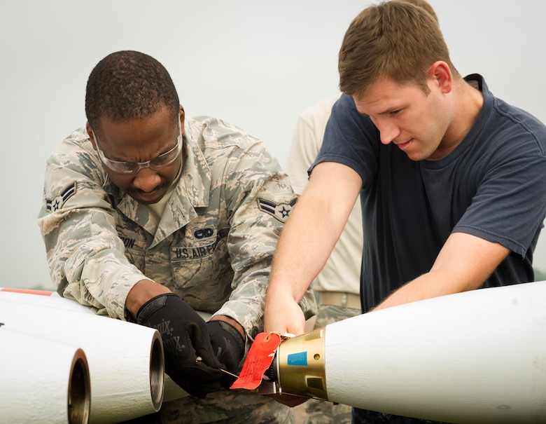 U.S. Airman 1st Class Eric Ligon, 5th Expeditionary Munitions Squadron crew chief, and Petty Officer 2nd Class Ray Charles Newman, Navy Munitions Command Unit Charleston mineman, cut arming wire to a MK-62 Quick Strike inert mine at Royal Air Force Fairford, United Kingdom, June 8, 2016. Navy minemen built 12 inert mines for a BALTOPS 16 exercise testing the B-52H Stratofortress' ability to precisely drop munitions into a target zone. (U.S. Air Force photo/Senior Airman Sahara L. Fales)