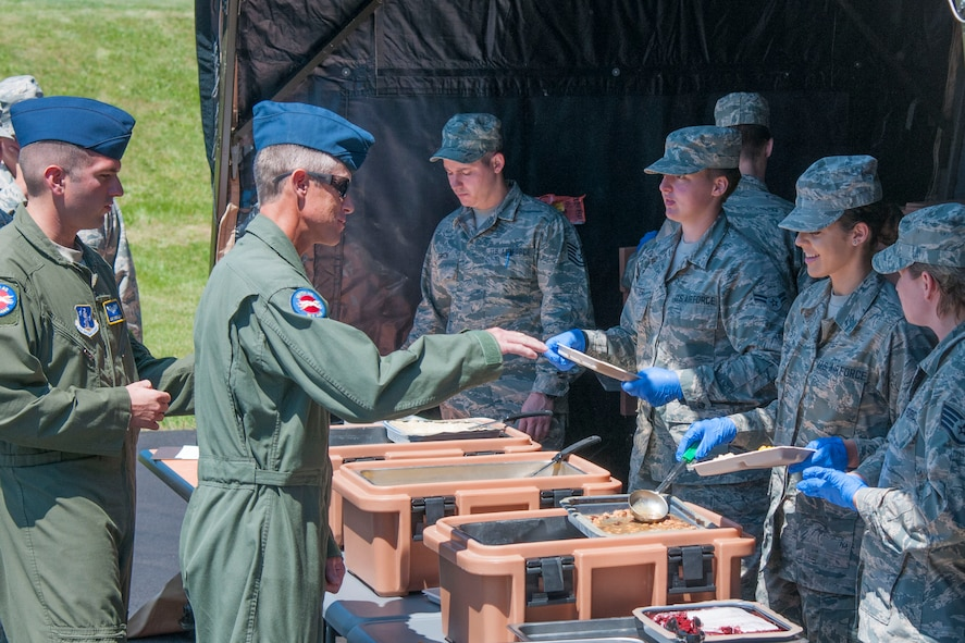 Master Sgt. Scott Miller (left), a loadmaster at the 167th Airlift Wing in Martinsburg, W.Va., receives his lunch from Airman 1st Class Shelby Alford, a services personnel at the 167th AW, June 10, 2016. Services took advantage of super drill to put up the Single Pallet Expeditionary Kitchen (SPEK). When the SPEK is fully put up it can seat 750 people. The food that is prepared comes in a unit group ration (UGR) that feeds 25 people. The UGR comes in three boxes and contains entrees, starch, paper products, and utensils. . (U.S. Air National Guard photo by Staff Sgt. Jodie Witmer)