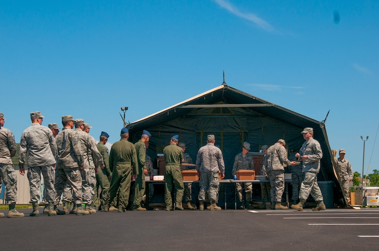Unit members at the 167th Airlift Wing in Martinsburg, W.Va. stood in line for lunch at the Single Pallet Expeditionary Kitchen (SPEK) that was put up by services members at super drill, June 10, 2016. The SPEK can be set up by 8 people in about 2 hours.  The apparatus that is used to heat the food is called a tray ration heater that is heated by a babington burner powered by diesel. (U.S. Air National Guard photo by Staff Sgt. Jodie Witmer)