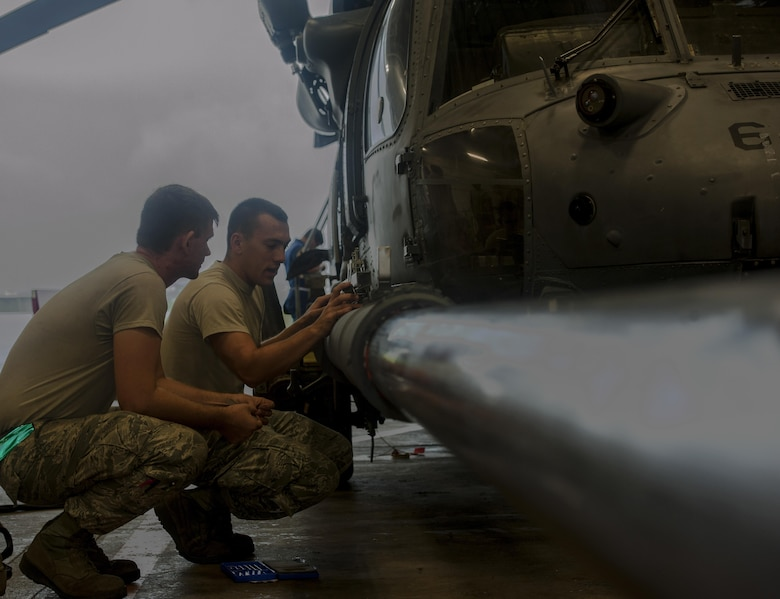 U.S. Air Force Staff Sgt. Cody Reigard and Airman 1st Class Zachary Zander, 33rd Helicopter Maintenance Unit crew chiefs, install a mount for a scale June 14, 2016, at Kadena Air Base, Japan. The scale showed the strength of the HH-60G Pave Hawk's fuel probe when pressure was applied to it. (U.S. Air Force photo by Airman 1st Class Lynette M. Rolen)