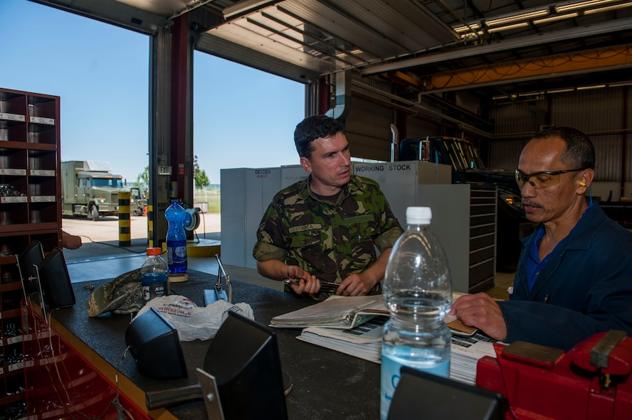 Romanian Land Forces Warrant Officer Bogden Cosma, Heavy Airlift Wing vehicle maintenance NCO-in-charge assigned to Papa Air Base, Hungary, left, speaks with Pedro Sagisi, the aircraft deicer qualification training course instructor, during the course at the European Transportation Training Center on Spangdahlem Air Base, Germany, June 9, 2016. Cosma supervises and manages a fleet of 35 ground transportation and flight line support vehicles that enable strategic airlift capabilities in Hungary. (U.S. Air Force photo by Airman 1st Class Timothy Kim/Released)