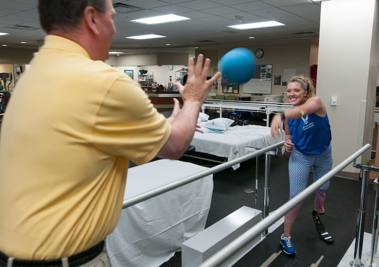 Heather Carter, an above-knee amputee, throws a ball to Bob Bahr, a physical therapist, during a therapy session inside the Military Advanced Training Center at Walter Reed National Military Medical Center in Bethesda, Md., April 13, 2016. Carter, a medically retired senior airman, and other amputees receive physical and occupational therapy at the center as they work toward their goals. One of Carter's goals is to return to competitive softball. (U.S. Air Force photo/Sean Kimmons)