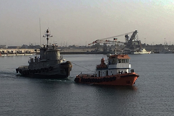 A contract tug begins its 12-hour journey from Kuwait Naval Base to the port of Doha, Qatar, with the retired Army tugboat in tow.
