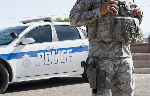 Staff Sgt. Agustin with the 49th Security Forces Squadron at Holloman Air Force Base, N.M., stands in front of his patrol car June 15. Since April 25, the 49th SFS has authorized selected personnel to be able to carry a concealed weapon while off duty and out of uniform. These changes are not the result of a direct threat, but address the everyday possibility of an active shooter incident occurring. (Last names are withheld due to operational constraints. U.S. Air Force photo by Airman 1st Class Randahl J. Jenson)