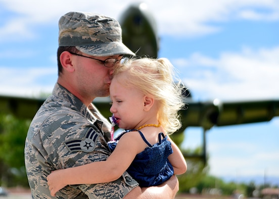 Senior Airman Christian Clauson, a 432nd Wing/432nd Air Expeditionary Wing photojournalist, kisses his daughter, Francesca, 2, at Nellis Air Force Base, Nev., June 9, 2016. Christian, who grew up as a military child, reflects on his transition from military child to military father. (U.S. Air Force photo/Tech. Sgt. Nadine Barclay)