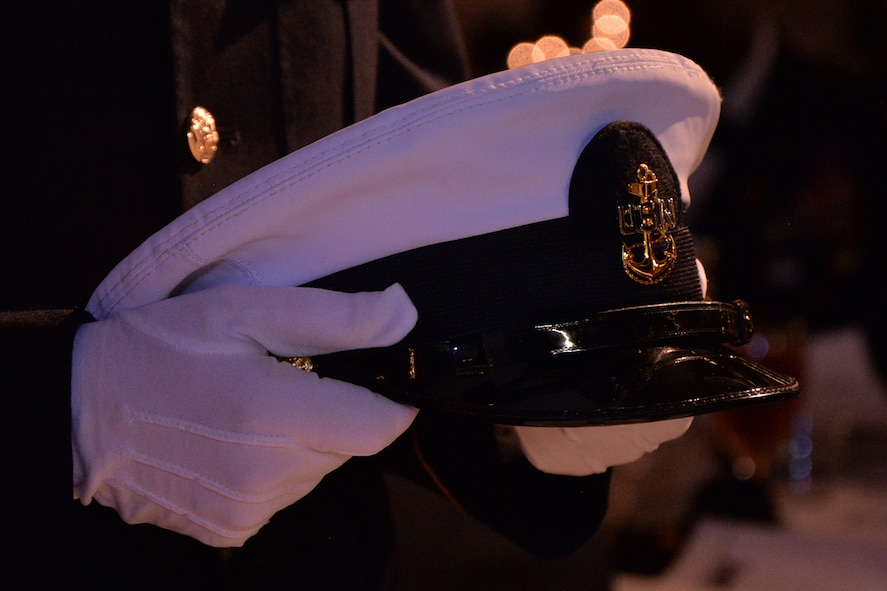 "An Honor Guard member places a U.S. Navy hat on the POW/MIA ""Missing Man"" table during the 344th Military Intelligence Battalion Army Ball at the Fort Concho Stables in San Angelo, Texas, June 10, 2016.  The table is set in remembrance of service members who are prisoners of war or missing in action. (U.S. Air Force photo by Airman 1st Class Randall Moose/Released)"