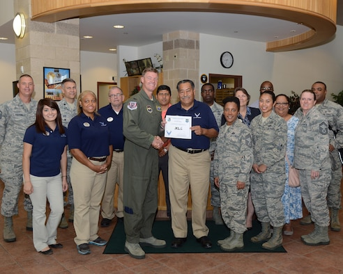 "Jose Gamez, center, 47th Force Support Squadron recreation aid, accepts the ""XLer of the Week"" award from Col. Thomas Shank, left, 47th Flying Training Wing commander, and Chief Master Sgt. Erica Shipp, right, 47th Mission Support Group superintendent, here, June 8, 2016. The XLer is a weekly award chosen by wing leadership and is presented to those who consistently make outstanding contributions to their unit and Laughlin. (U.S. Air Force photo/Airman 1st Class Brandon May)"