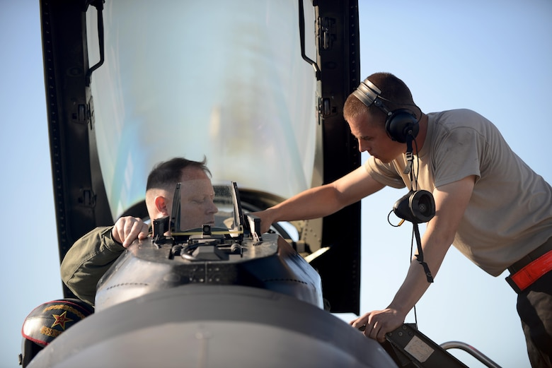U.S. Air Force Airman 1st Class Michael Brinkmeyer (left), an F-16 Fighting Falcon assistant dedicated crew chief with the18th Aircraft Maintenance Unit, secures U.S. Air Force Maj. Scott Meng, 18th Aggressor Squadron F-16 Fighting Falcon pilot, during RED FLAG-Alaska 16-2, on Eielson Air Force Base, Alaska, June 15, 2016. (U.S. Air Force photo by Tech. Sgt. Steven R. Doty)