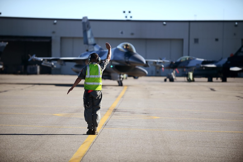 U.S. Air Force Staff Sgt. Nathaniel Moore, an F-16 Fighting Falcon dedicated crew chief with the18th Aircraft Maintenance Unit, marshals an F-16 for end-of-ramp operations during RED FLAG-Alaska 16-2, on Eielson Air Force Base, Alaska, June 15, 2016. (U.S. Air Force photo by Tech. Sgt. Steven R. Doty)