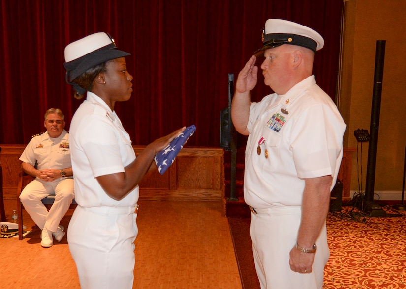 Command Master Chief Joseph Gardner receives a flag as part of his retirement ceremony, June 10, 2016, at the Joint Base Charleston – WS, Red Bank Club. Gardner served for more than 28 years in the United States Navy. (U.S. Navy Photo by Mass Communication Specialist Sean M. Stafford/Released)