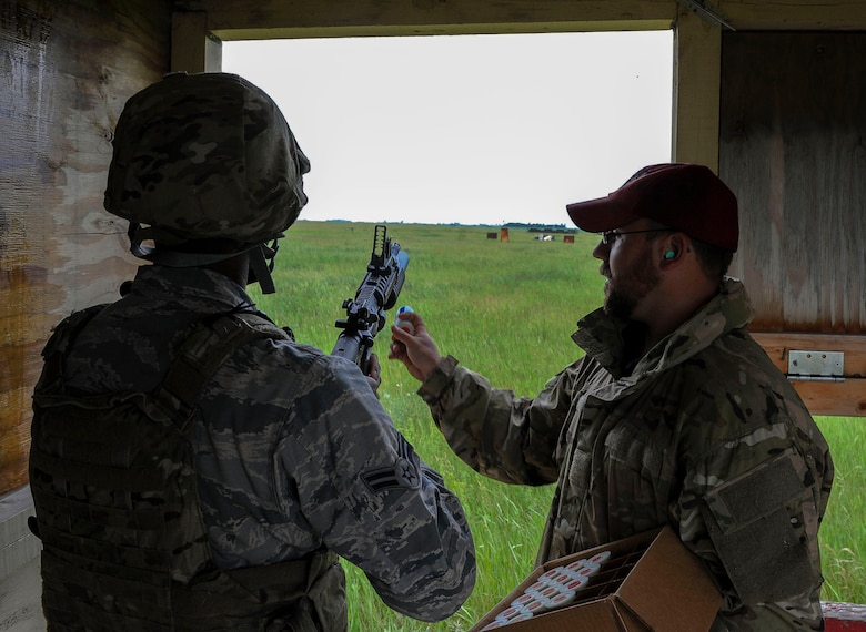 Jeremy Smith, Combat Arms instructor, loads an M-203 grenade launcher cartridge into a weapon during annual firing for defenders at Minot Air Force Base, N.D., June 15, 2016. Prior to firing, the defenders learned how to break down the M-203 and clean it. To carry the weapon, defenders must qualify annually. (U.S. Air Force photo/Senior Airman Kristoffer Kaubisch)