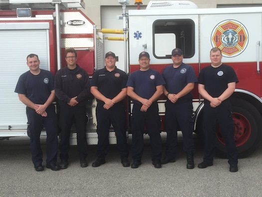 A team of firefighters from the 115th Fighter Wing Truax Fire and Emergency Services pose for a photo outside thier fire truck in Madison, Wis., June 6, 2016. This team of firefighters helped save a woman's life by performing cardiopulmonary resuscitation, a lifesaving technique used when someone's hearbeat has stopped or that person is not breathing. (Photo courtesy of Master Sgt. Gary Peck)