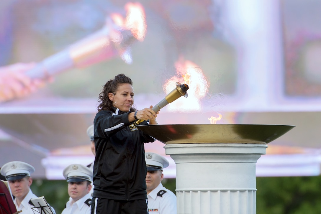 Army Capt. Kelly Elminger lights the 2016 Department of Defense Warrior Games torch during opening ceremonies for the games at the U.S. Military Academy in West Point, N.Y., June 15, 2016. (Department of Defense photo/EJ Hersom)