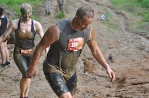 Stephen Lynch of Dumfries, Virginia and Christine Hanke of Arlington, Virginia are all smiles coming out of the steep mud pit at the end of the course.
